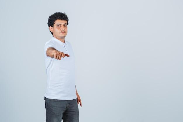 Junger mann streckt die hand in richtung kamera in weißem t-shirt und jeans und sieht ernst aus, vorderansicht.