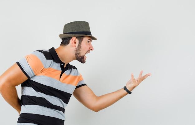 Junger mann streckt hand in fragender weise in t-shirt, hut und sieht wütend aus. .