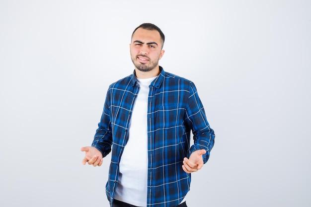 Junger mann streckt sich fragend die hände in kariertem hemd und weißem t-shirt aus und sieht verwirrt