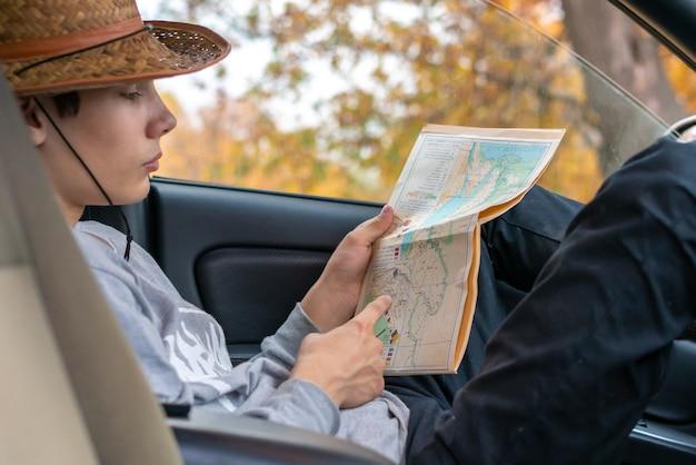 Junger mann sucht den weg mit einer karte im auto sitzen