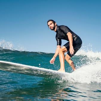 Junger mann surft ozeanwellen
