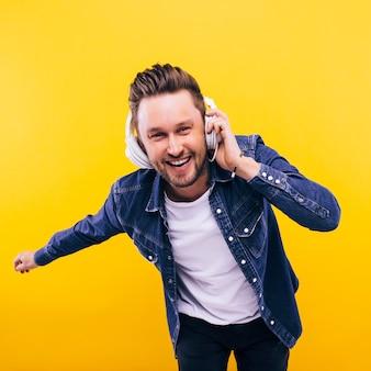 Junger mann tanzt und hört musik. emotionen, mimik, gefühle, körpersprache, zeichen. bild auf einem gelben studiohintergrund.