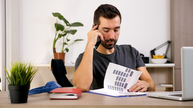 Junger mann telefoniert, während er im büro ist. intelligenter mann, der sich um das geschäft kümmert.