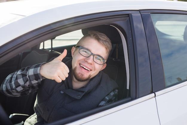 Junger mann testet neues auto und zeigt daumen hoch