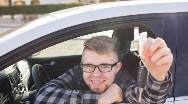 Junger mann testet neues auto und zeigt schlüssel. autokauf oder mietkonzept.
