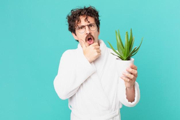 Junger mann trägt bademantel mit mund und augen weit geöffnet und hand am kinn