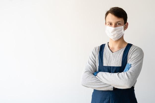 Junger mann trägt ein medizinisches gesicht und eine uniform. arbeiten sie während einer pandemie und quarantäne.