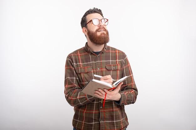 Junger mann träumt von etwas und schreibt in sein tagebuch über leerraum.