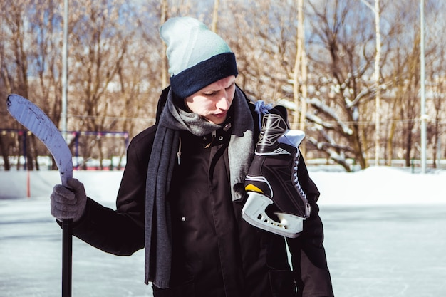Junger mann tragen schlittschuhe und hickey-stick auf einer eisbahn