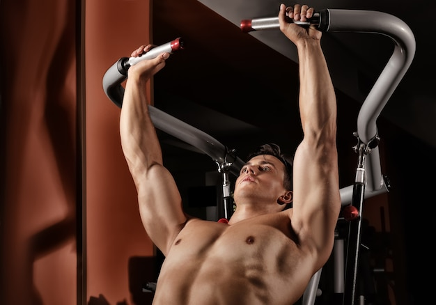 Junger mann trainiert am trainingsgerät im fitnessstudio