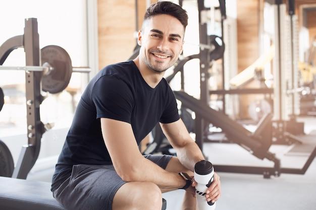 Junger mann trainiert im fitnessstudio gesunden lebensstil