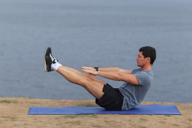 Junger mann trainiert im freien und macht sit-ups im freien