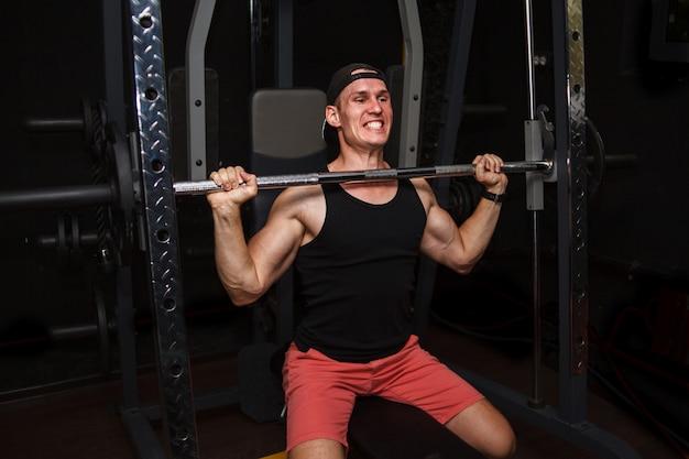 Junger mann trainiert seinen rücken in der turnhalle.