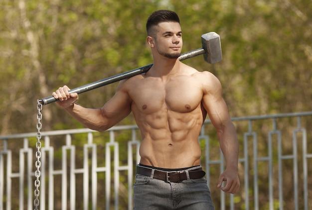 Junger mann trifft reifen - training im freien mit hammer