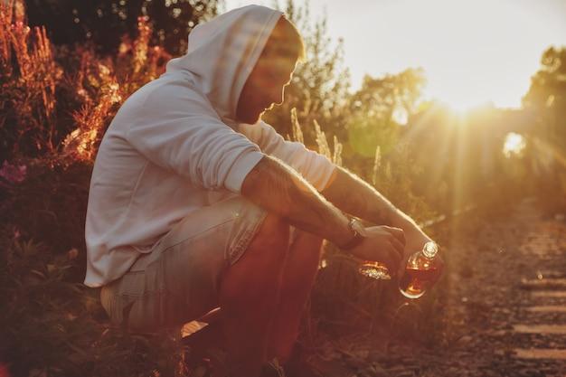 Junger mann trinkt alkohol auf einer verlassenen eisenbahn in der landschaft bei sonnenuntergang. konzept der traurigkeit, apathie, depression oder eines falschen lebensstils. platz kopieren
