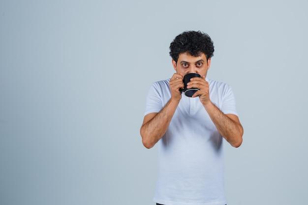 Junger mann trinkt eine tasse tee in weißem t-shirt und jeans und sieht durstig aus, vorderansicht.