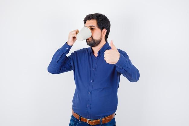 Junger mann trinkt eine tasse wasser und zeigt daumen in blauem hemd und jeans und sieht optimistisch aus. vorderansicht.