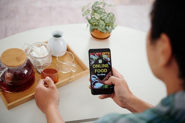 Junger mann trinkt schwarzen tee und bestellt essenslieferungen über die app auf dem smartphone