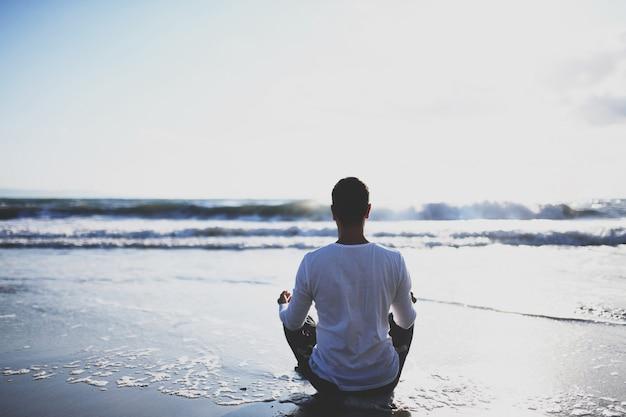 Junger mann üben yoga am strand bei sonnenuntergang.