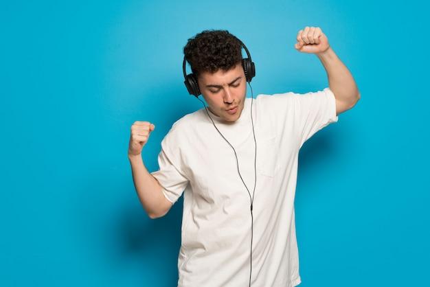 Junger mann über blau hörend musik mit kopfhörern und tanzen
