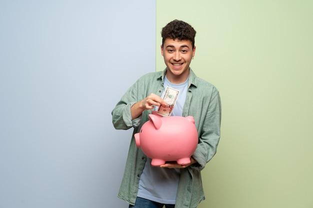 Junger mann über blau und grün ein sparschwein nehmend und glücklich, weil es voll ist
