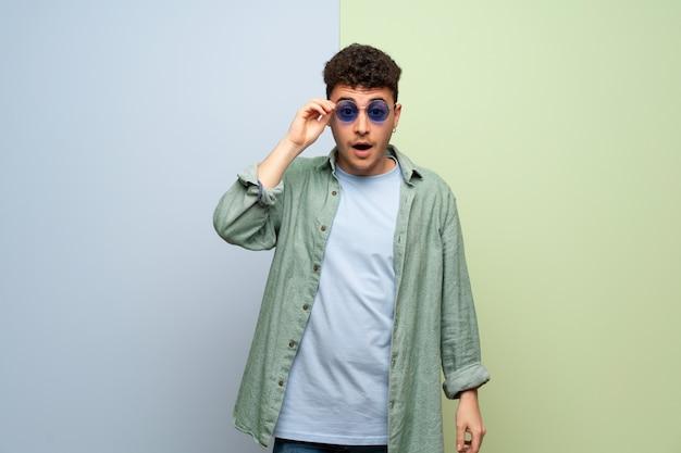 Junger mann über blau und grün mit brille und überrascht