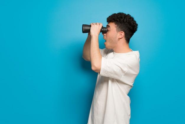 Junger mann über blau und in der ferne mit einem fernglas suchen