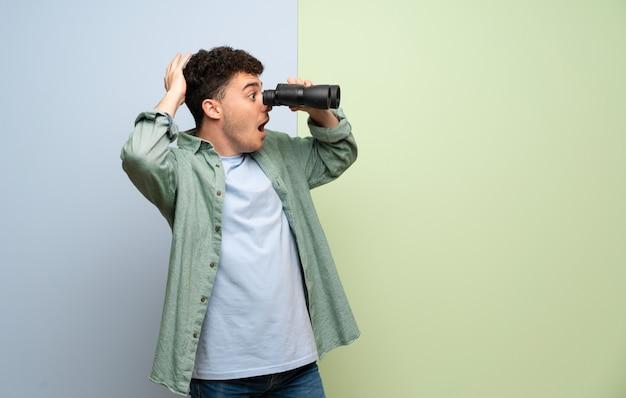Junger mann über blauem und grünem und schauen im abstand mit ferngläsern