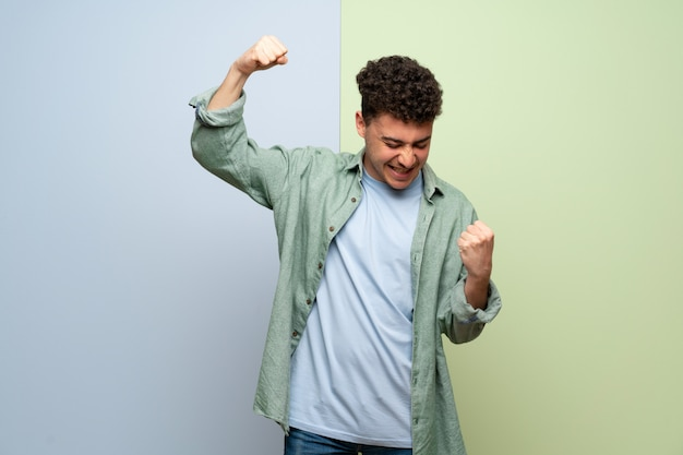 Junger mann über blauer und grüner wand einen sieg feiernd