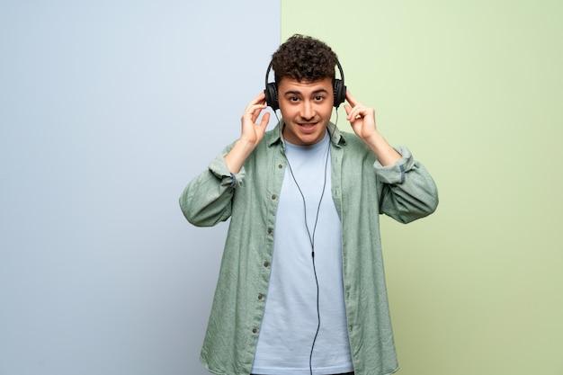 Junger mann über blauer und grüner wand hörend musik mit kopfhörern