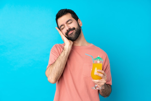 Junger mann über das halten eines cocktails, der schlafgeste im liebenswerten ausdruck macht