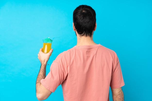 Junger mann über das halten eines cocktails in der hinteren position