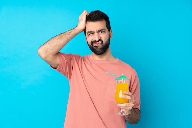 Junger mann über das halten eines cocktails mit einem ausdruck der frustration und des nichtverständnisses