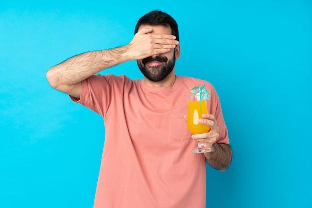 Junger mann über das halten eines cocktails über isolierte blaue wand, die augen durch hände bedeckt