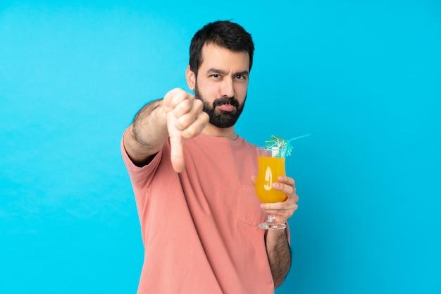 Junger mann über das halten eines cocktails über isolierte blaue wand, die daumen unten mit negativem ausdruck zeigt