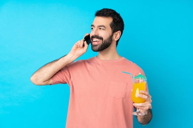 Junger mann über das halten eines cocktails über isolierte blaue wand, die ein gespräch mit dem mobiltelefon hält