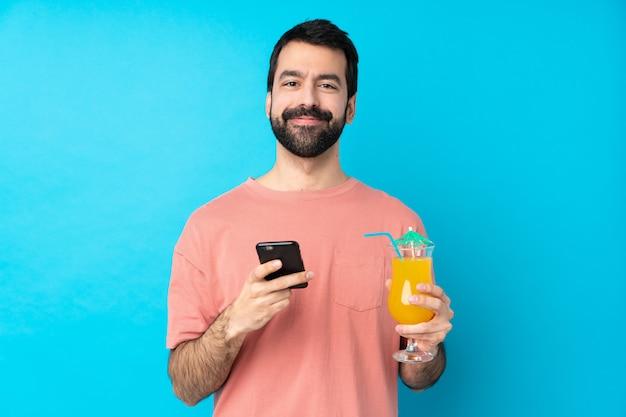 Junger mann über das halten eines cocktails über isolierte blaue wand, die eine nachricht mit dem handy sendet