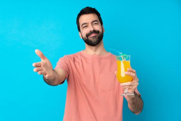 Junger mann über das halten eines cocktails über isolierte blaue wand, die präsentiert und einlädt, mit hand zu kommen