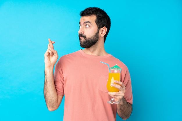Junger mann über das halten eines cocktails über isolierte blaue wand mit den fingern, die kreuzen und das beste wünschen