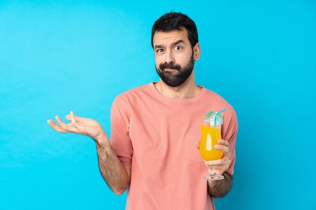 Junger mann über das halten eines cocktails über isolierte blaue wand unglücklich, etwas nicht zu verstehen