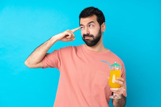 Junger mann über das halten eines cocktails über isolierter blauer wand, die die geste des wahnsinns macht, der finger auf den kopf setzt