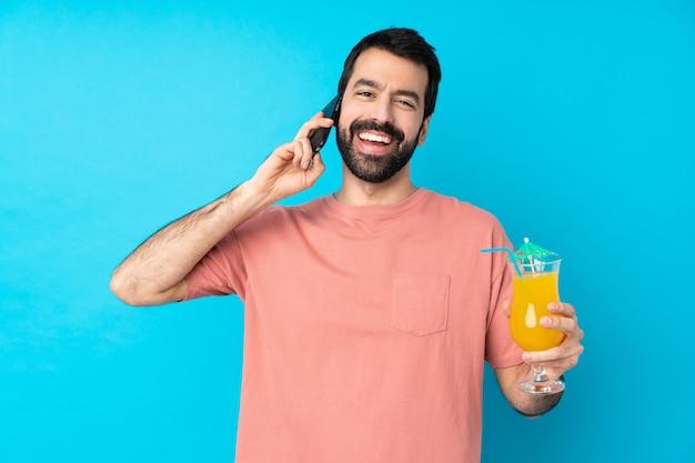 Junger mann über das halten eines cocktails über isolierter blauer wand, die ein gespräch mit dem mobiltelefon mit jemandem hält