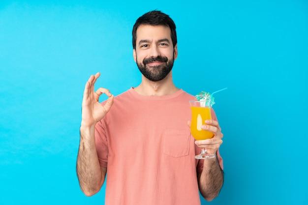 Junger mann über das halten eines cocktails über isolierter blauer wand, die ein ok-zeichen mit fingern zeigt