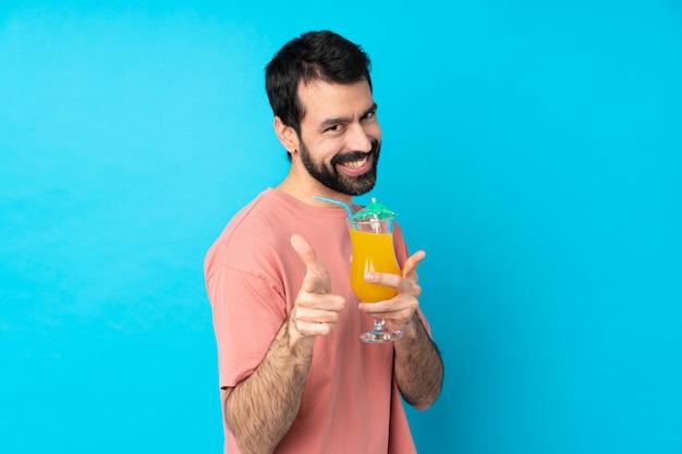 Junger mann über das halten eines cocktails über isolierter blauer wand, die nach vorne zeigt und lächelt
