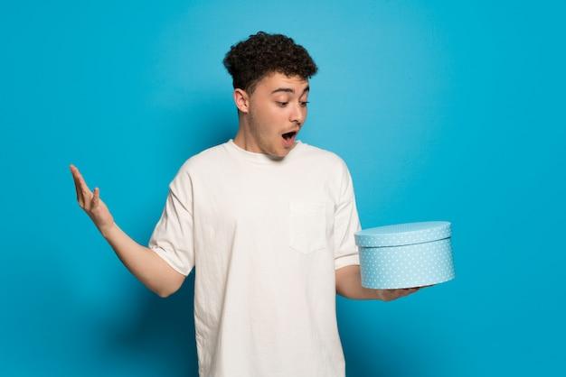 Junger mann über dem blauen hintergrund, der geschenkbox in den händen hält