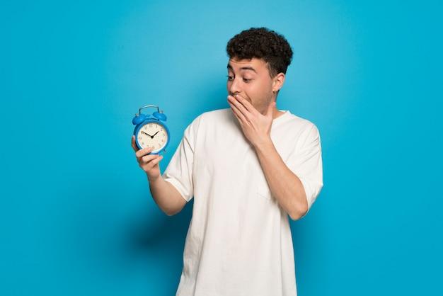 Junger mann über dem blauen hintergrund, der weinlesewecker hält