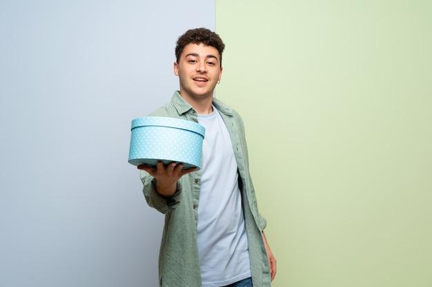 Junger mann über der blauen und grünen wand, die ein geschenk in den händen hält