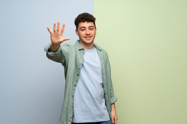 Junger mann über der blauen und grünen wand, die fünf mit den fingern zählt