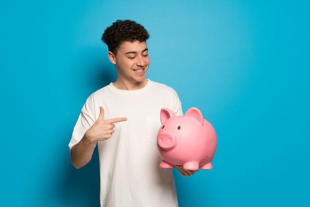 Junger mann über der blauen wand, die ein sparschwein hält