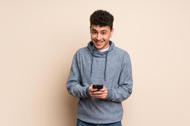 Junger mann über der lokalisierten wand, die eine mitteilung mit dem mobile sendet